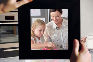 Female hand framing mother and daughter baking together in kの写真素材 [FYI03647191]