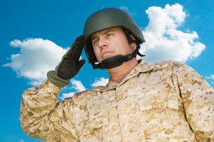 Mid-adult soldier in military uniform saluting against cloudの写真素材 [FYI03647211]