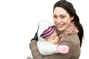 Portrait of beautiful mother holding baby girl against whiteの写真素材 [FYI03647214]