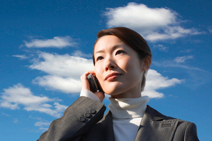 Young businesswoman using cell phone against cloudy skyの写真素材 [FYI03647253]