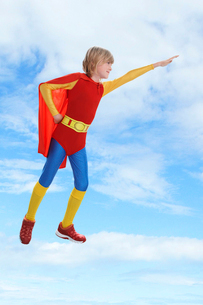 Boy dressed as superhero flying against cloudy skyの写真素材 [FYI03647271]