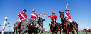 Multiethnic polo team celebrating with trophy on fieldの写真素材 [FYI03647299]