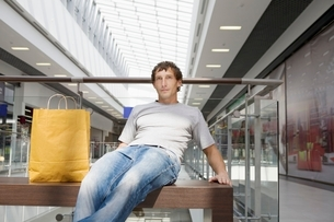 Young man sits in new shopping centre Voronezhの写真素材 [FYI03647325]
