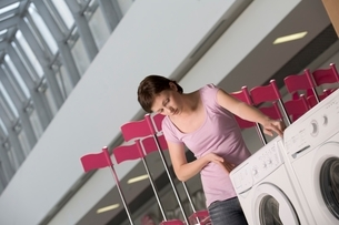 Young woman measures washing machine in shopping mall Voroneの写真素材 [FYI03647333]