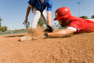 Runner and infielder reaching baseの写真素材 [FYI03647355]