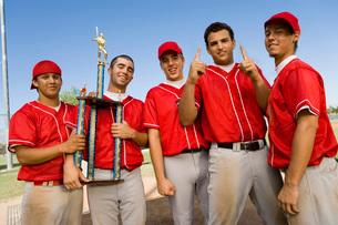 Baseball team-mates holding trophy on fieldの写真素材 [FYI03647359]