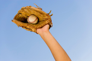 Baseball player catching ball in baseball glove close-up ofの写真素材 [FYI03647378]