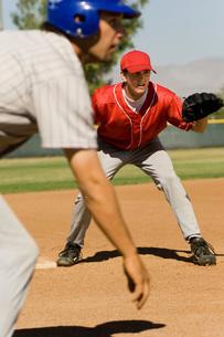 Baseball fielder and runner on field preparing to gameの写真素材 [FYI03647399]