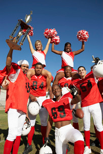 Football players and cheerleaders holding up trophyの写真素材 [FYI03647403]