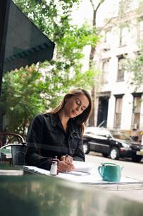 Woman writing at sidewalk cafeの写真素材 [FYI03647434]