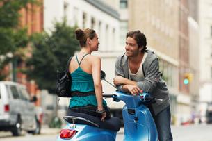 Woman on moped talking to man in streetの写真素材 [FYI03647440]
