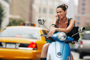 Woman using mobile phone on mopedの写真素材 [FYI03647441]