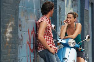 Woman on moped talking to man in streetの写真素材 [FYI03647442]