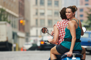 Couple riding on moped in streetの写真素材 [FYI03647443]