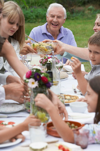 Multigenerational family dining in gardenの写真素材 [FYI03647499]