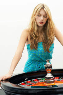 Young woman standing at roulette wheelの写真素材 [FYI03647507]