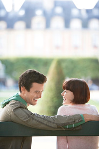 Young couple sitting on bench looking over shoulder in parkの写真素材 [FYI03647519]