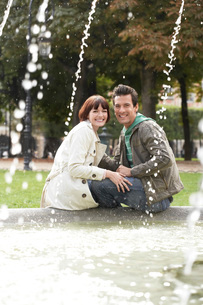 Couple sitting on edge of fountain view past water jetsの写真素材 [FYI03647524]