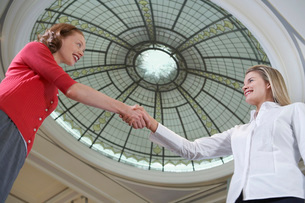 Two women shaking hands under dome low angle viewの写真素材 [FYI03647565]