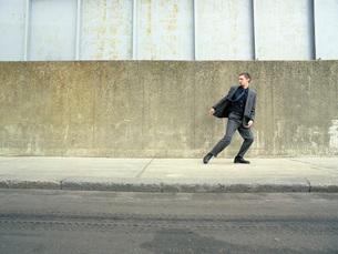Teenager in suit running on street looking backの写真素材 [FYI03647633]