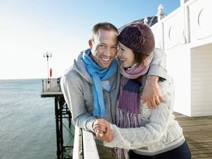 Couple holding hands standing on pier portraitの写真素材 [FYI03647657]