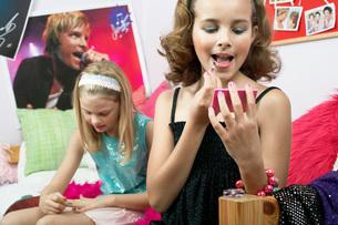 Fashionable Young Girls Applying Makeup in trendy bedroomの写真素材 [FYI03647683]