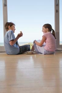 Young girl and boy sitting on floor in doorway eating sandwiの写真素材 [FYI03647690]