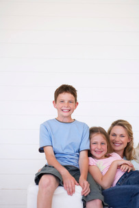 Portrait of mother and children sitting on couch in weatherの写真素材 [FYI03647701]