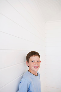 Young boy standing against weather boarded wall portraitの写真素材 [FYI03647704]