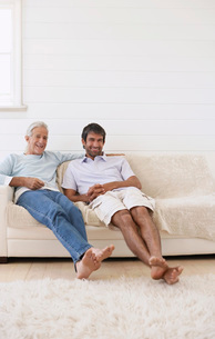 Two men sitting on sofa in weather boarded roomの写真素材 [FYI03647706]