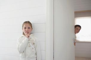 Girl with finger on lips standing by boy peeking round doorの写真素材 [FYI03647712]