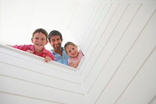 Father with son and daughter looking over white wall view frの写真素材 [FYI03647723]