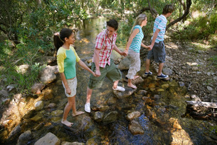 Four teenagers (16-17) crossing stream holding hands elevateの写真素材 [FYI03647760]