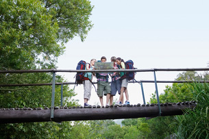 Four teenagers (16-17 years) backpacking in forest reading mの写真素材 [FYI03647768]