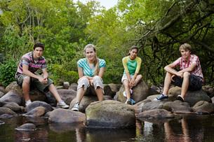 Portrait of four teenagers (16-17 years) sitting on stones bの写真素材 [FYI03647771]
