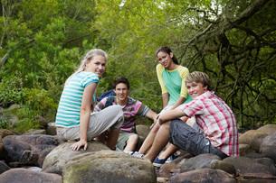 Portrait of four teenagers (16-17 years) sitting on stones bの写真素材 [FYI03647774]