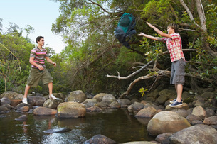 Two teenage boys (16-17 years) standing on stones by river tの写真素材 [FYI03647778]