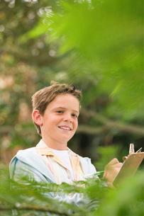 Boy Writing in Forestの写真素材 [FYI03647784]
