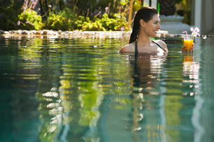 Young woman holding drink in natural swimming pool portraitの写真素材 [FYI03647826]