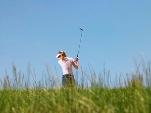 Young female golfer driving ball back viewの写真素材 [FYI03647846]