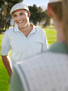 Young golfers on course focus on smiling manの写真素材 [FYI03647865]