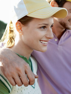 Two young golfers on court focus on smiling womanの写真素材 [FYI03647876]