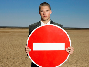 Businessman holding 'no entry' sign in desert half lengthの写真素材 [FYI03647883]
