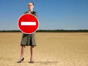Businesswoman holding 'no entry' sign in desert full lengthの写真素材 [FYI03647889]