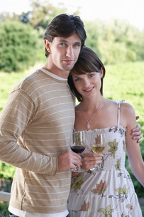 Young couple on terrace holding wine glassesの写真素材 [FYI03647926]