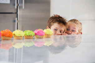 Young girl and boy peeking over counter at row of cupcakes hの写真素材 [FYI03647960]