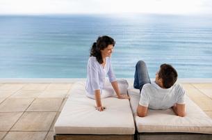 Couple relaxing on sun beds on terrace overlooking sea elevaの写真素材 [FYI03648024]