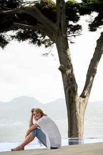 Woman sitting on floor by infinity pool side viewの写真素材 [FYI03648025]