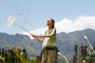 Girl (7-9) standing in field holding butterfly net low angleの写真素材 [FYI03648026]