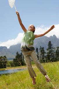 Girl (7-9) in field reaching towards sky with butterfly net.の写真素材 [FYI03648028]